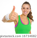 Closeup on fitness young woman showing thumbs up 16734682