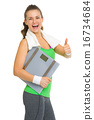 Smiling fitness young woman with scales showing thumbs up 16734684