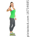 Smiling fitness young woman standing on scales and showing thumb 16734685