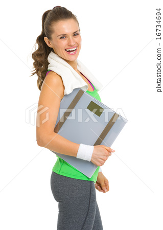 Portrait of smiling fitness young woman with scales 16734694