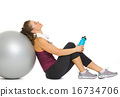 Tired fitness young woman relaxing after workout on fitness ball 16734706