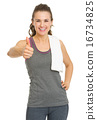 Smiling fitness young woman showing thumbs up 16734825