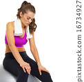 Tired young woman sitting on fitness ball 16734927