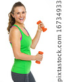 Portrait of smiling fitness young woman with dumbbells 16734933