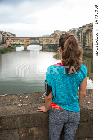 Fitness woman looking on ponte vecchio in florence, italy. rear 16735099