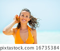 Portrait of happy young woman listening sound of sea in shell on 16735384