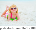 Portrait of baby girl in sunglasses laying on beach 16735388