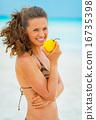 Portrait of happy young woman eating pear on beach 16735398