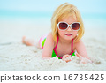 Portrait of baby girl in sunglasses laying on beach 16735425