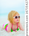 Portrait of baby girl in sunglasses laying on beach 16735427
