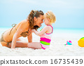 Portrait of smiling mother and baby girl playing on beach 16735439