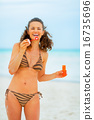 Smiling young woman blowing soap bubbles on beach 16735696