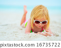 Baby girl in sunglasses laying on beach 16735722