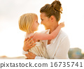 Portrait of happy mother and baby girl hugging on beach at the e 16735741