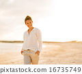 Portrait of happy young woman on beach at the evening 16735749