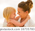 Portrait of smiling mother and baby girl hugging on beach at the 16735783