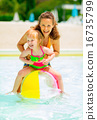 Portrait of happy mother and baby girl playing with beach ball i 16735799