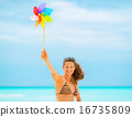 Smiling young woman showing colorful windmill toy on beach 16735809