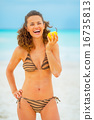 Portrait of happy young woman with pear on beach 16735813