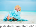 Portrait of laughing baby girl wrapped in towel sitting on beach 16735823