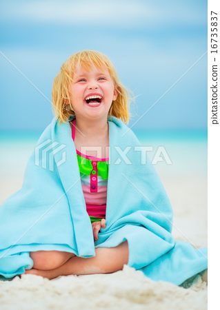 Portrait of laughing baby girl wrapped in towel sitting on beach 16735837