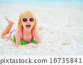 Portrait of happy baby girl in sunglasses laying on beach 16735841