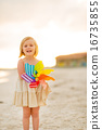 Portrait of smiling baby girl holding colorful windmill toy on b 16735855