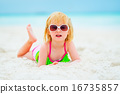 Portrait of baby girl in sunglasses laying on beach 16735857