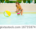 Happy mother and baby girl playing with beach ball in pool 16735874