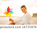 Portrait of smiling young woman with colorful windmill toy sitti 16735876