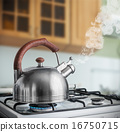 kettle boiling on a gas stove in the kitchen 16750715