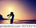 cheering young woman open arms on sunrise beach 16759378