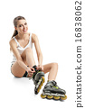 Pretty happy girl with rollerskates sitting on floor against white background 16838062
