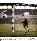 boy plays football on stadium 16859253