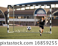 boy plays football on stadium 16859255