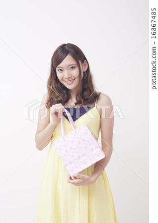 A woman holding a shopping bag 16867485