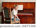 little boy plays piano at home 16875366