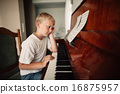 boy plays piano at home 16875957