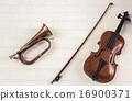 Old trumpet and violin hang on brick wall 16900371