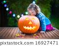 Little girl carving pumpkin at Halloween 16927471