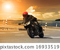 young man riding big bike motorcycle against sharp curve of asph 16933519