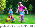 Two children riding bikes 16958103