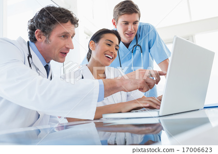 Stock Photo: Team of happy doctors working on laptop computer