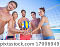 Group of friends holding volleyball and smiling at camera 17006949