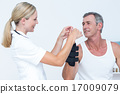 Doctor examining a man wrist 17009079