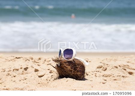 Coconut  and a sunglasses on a beautiful beach. 17095096