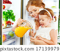 happy family mother and baby daughter drinking orange juice in 17139979