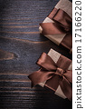 Giftboxes with brown ribbons on vintage wood board 17166220