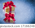 Packed golden gifts with red bows on scratched metallic backgrou 17166248