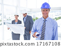 Businessmen and a woman with hard hats and holding blueprint 17167108